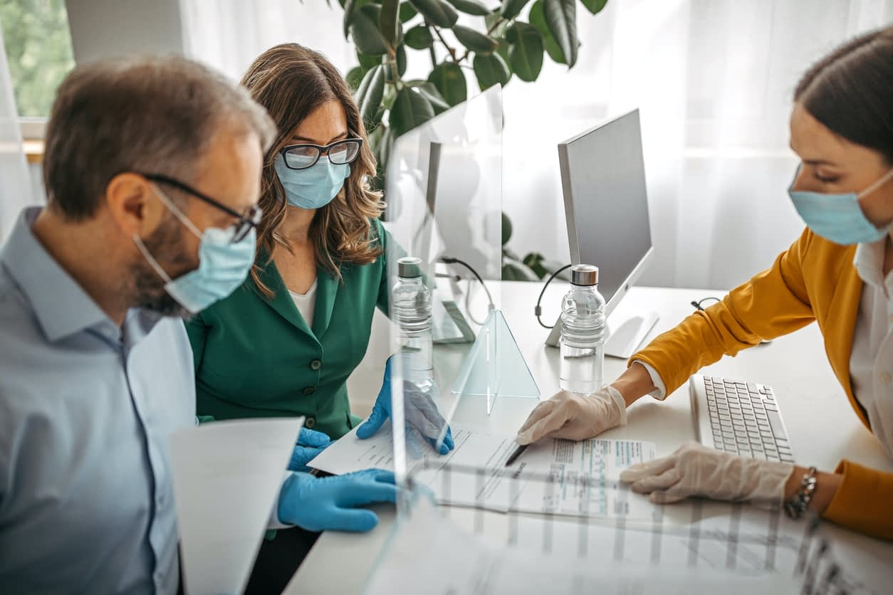 Financial advisor explaining contract to customers wearing protective gloves and face mask stock photo