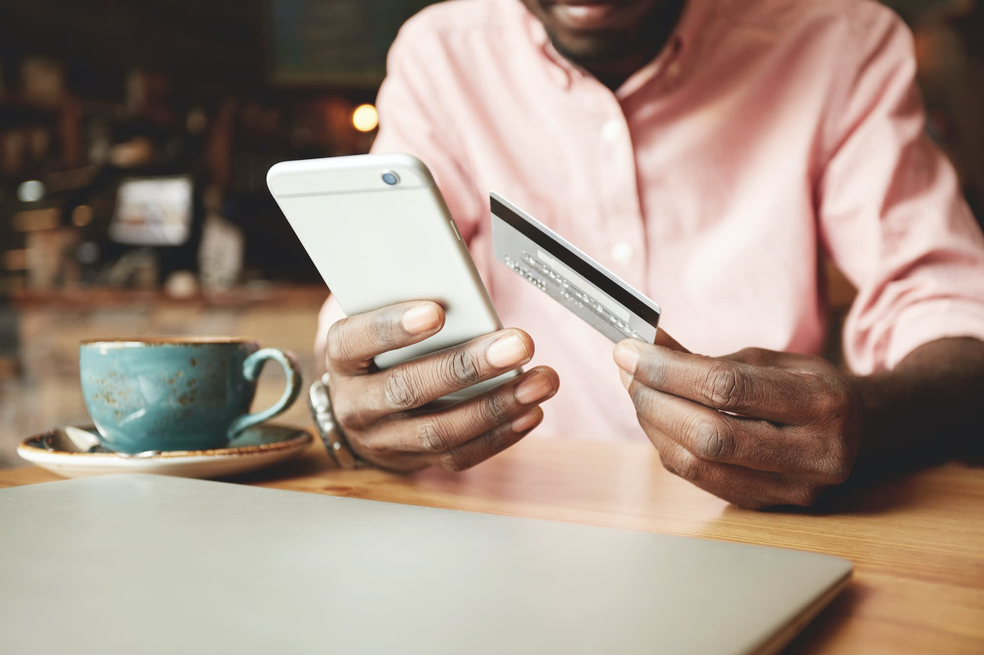 African American man in casual shirt paying with credit card online while making orders via the Internet. Successful black businessman making transaction using mobile bank application.