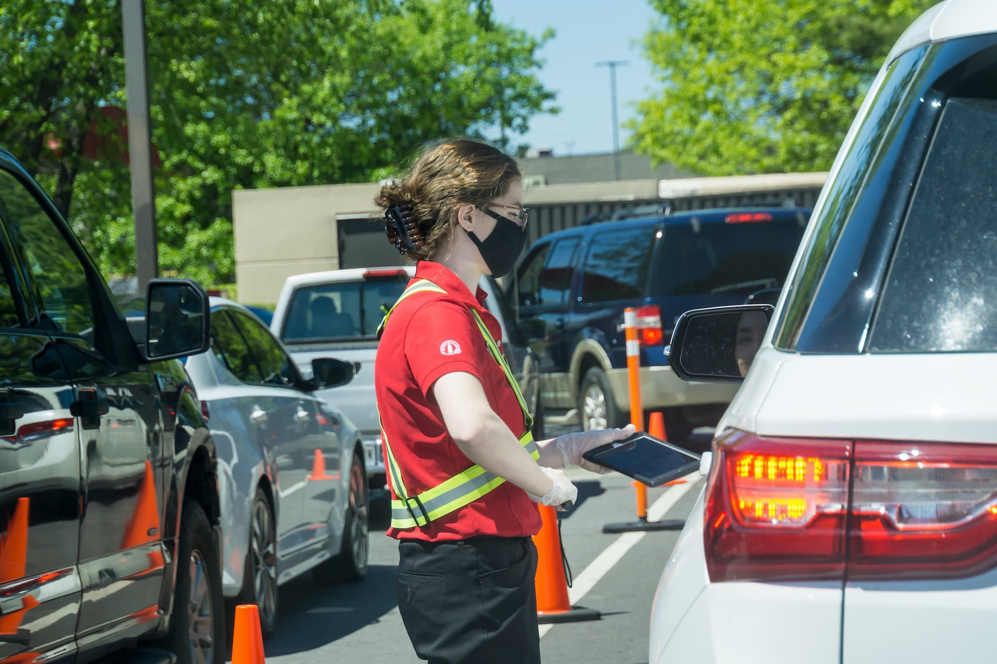 Young youthful fast food worker working at Chick-fil-a drive through amidst cars take orders with tablet.