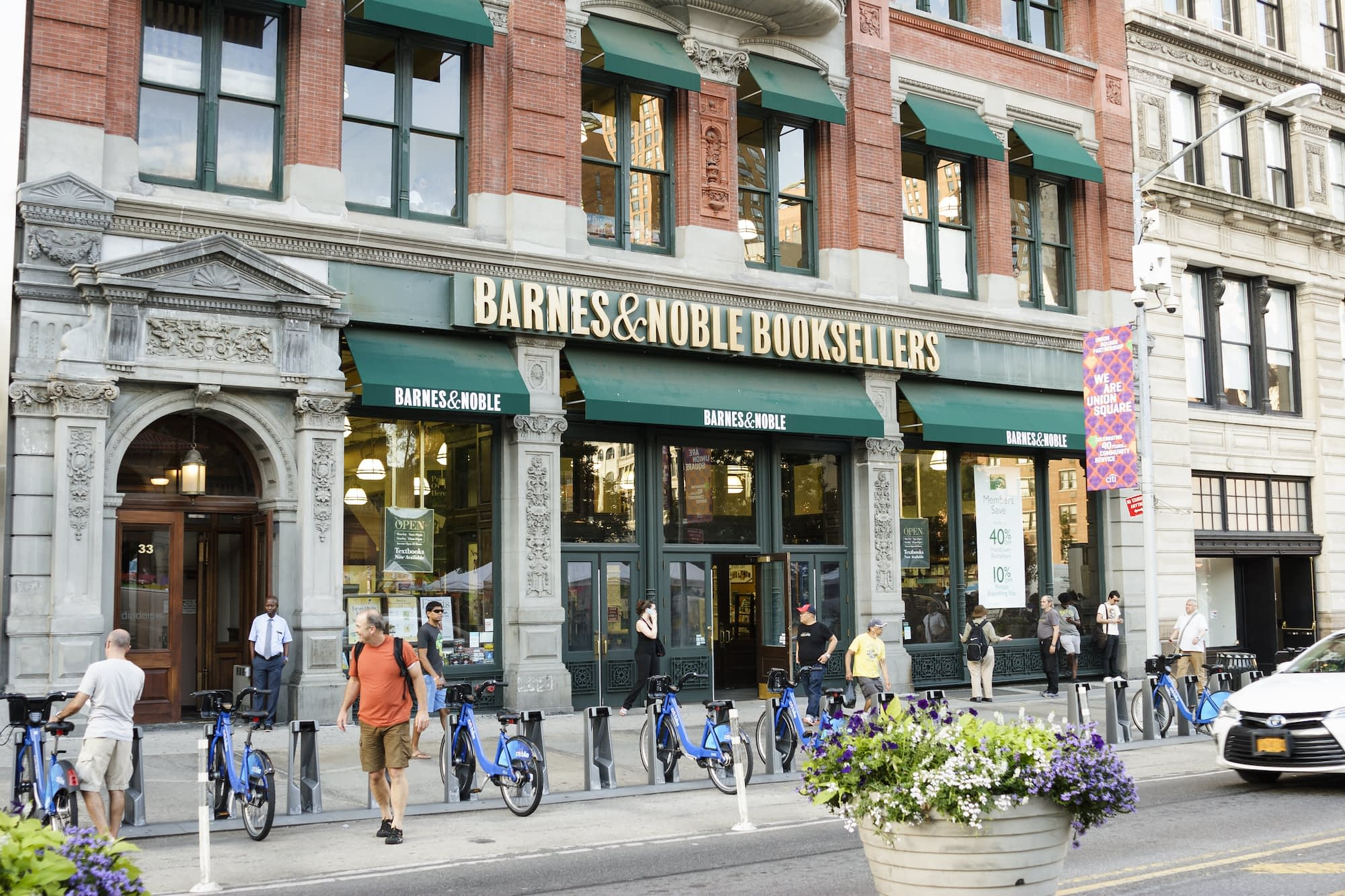 A Barnes and Noble store across the street from Union Square Park. People can be seen.