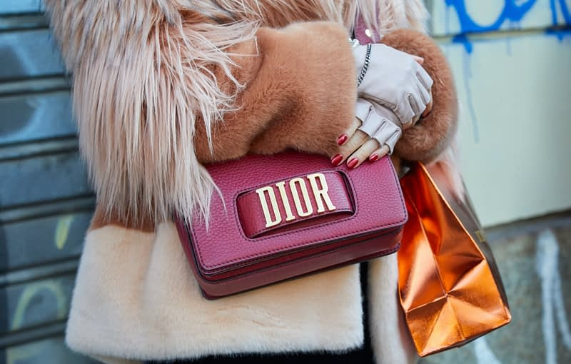 Woman with red leather Dior bag and brown pink fur coat before John Richmond fashion show, Milan Fashion Week street style