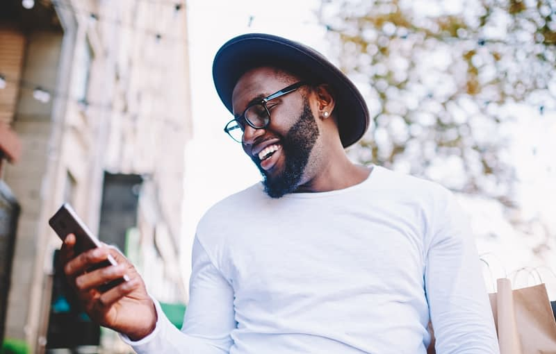Cheerful African American man in white shirt using mobile phone application for searching cafes near location in downtown, happy dark skinned hipster guy read news from social network walking in city