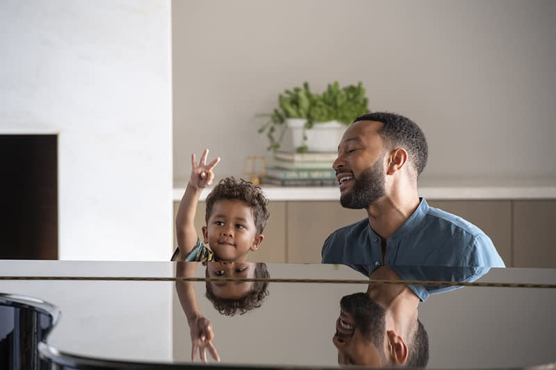 John Legend plays piano with his son sitting beside him in a new Vrbo commercial