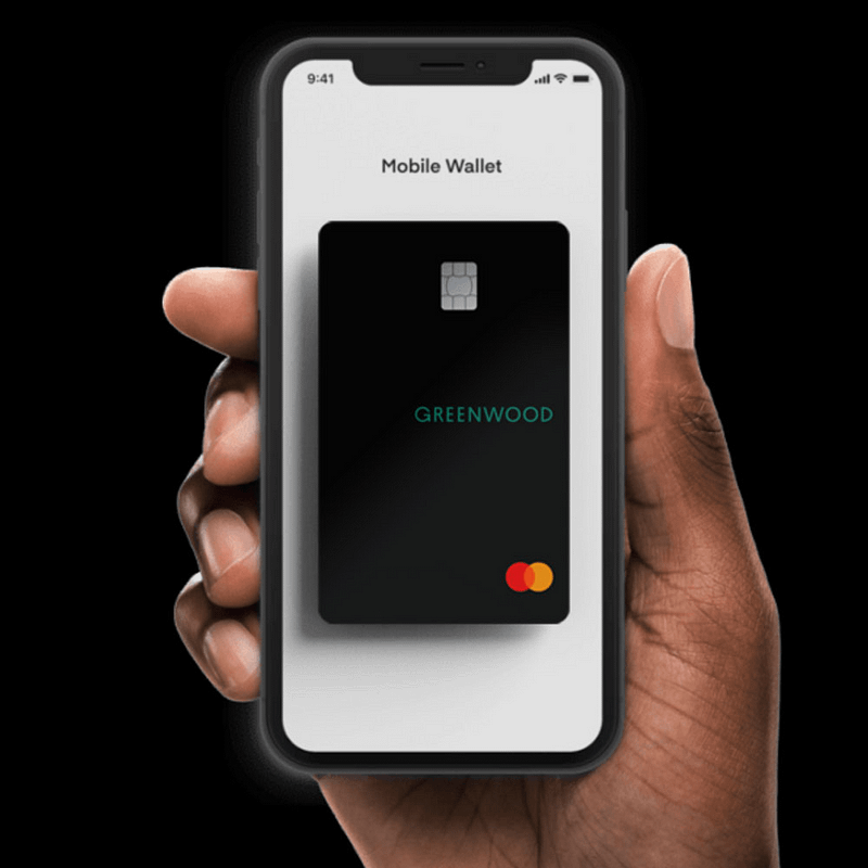 black person holding a phone with a picture of a Greenwood bank card on the screen